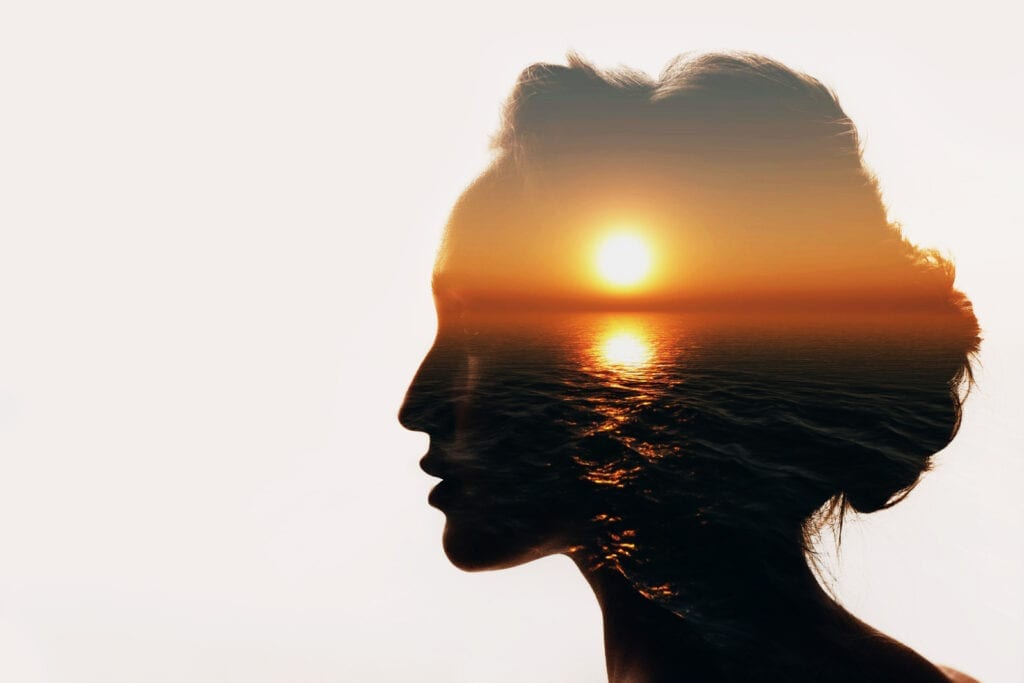 Background image of woman silhouette revealing an ocean sunset